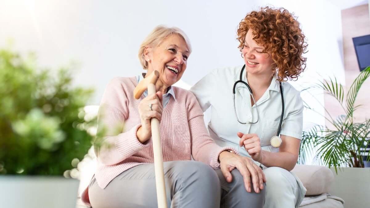 eine Rentnerin sitzt mit einem Gehstock, als Alltagshilfe, neben ihrer Betreuerin