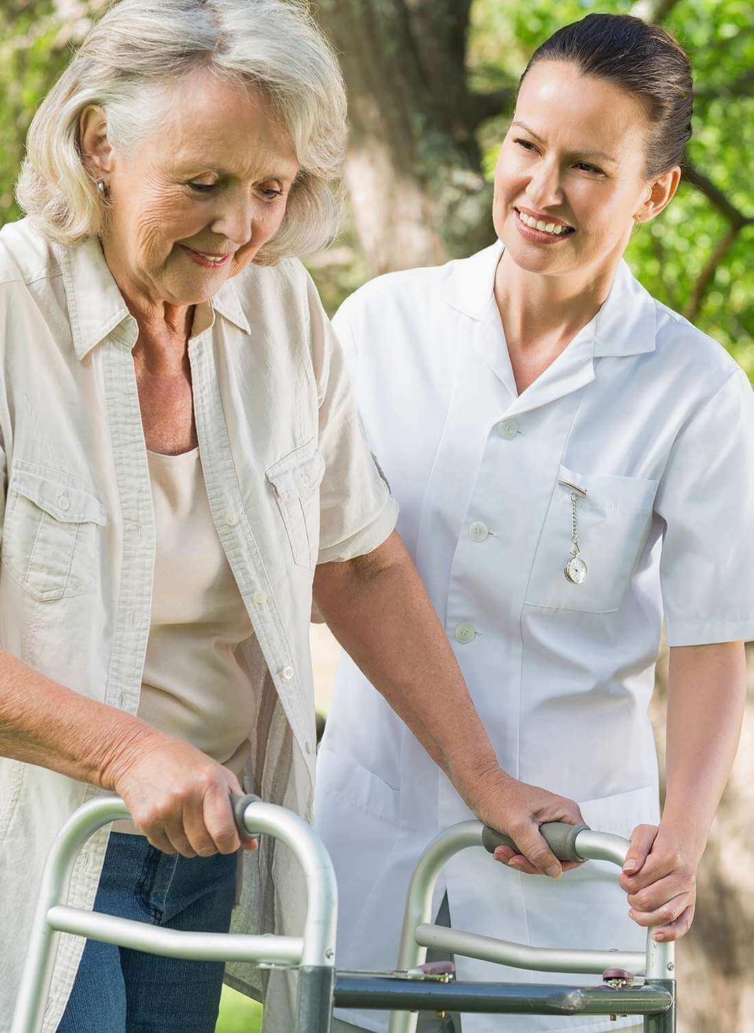 Pflegende der Spitex Arlesheim begleitet eine Seniorin mit Gehhilfe auf einen Spaziergang.