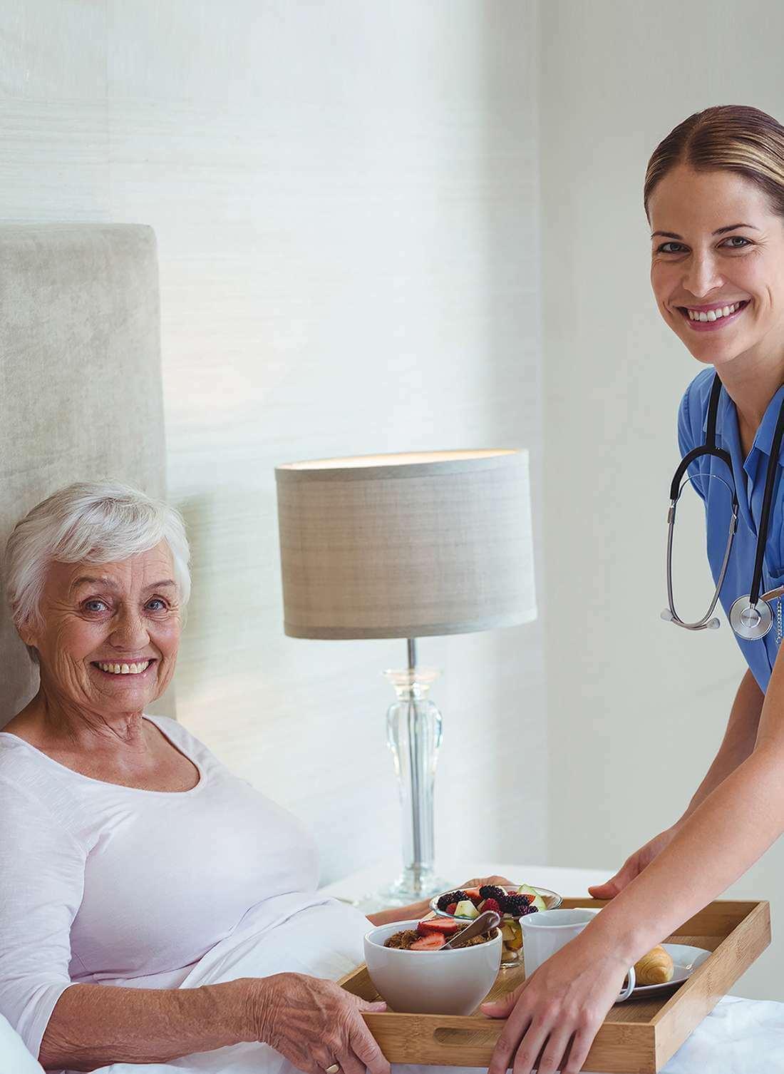 Lächelnde Krankenschwester, die einer älteren Frau das Frühstück an ihr Bett serviert.