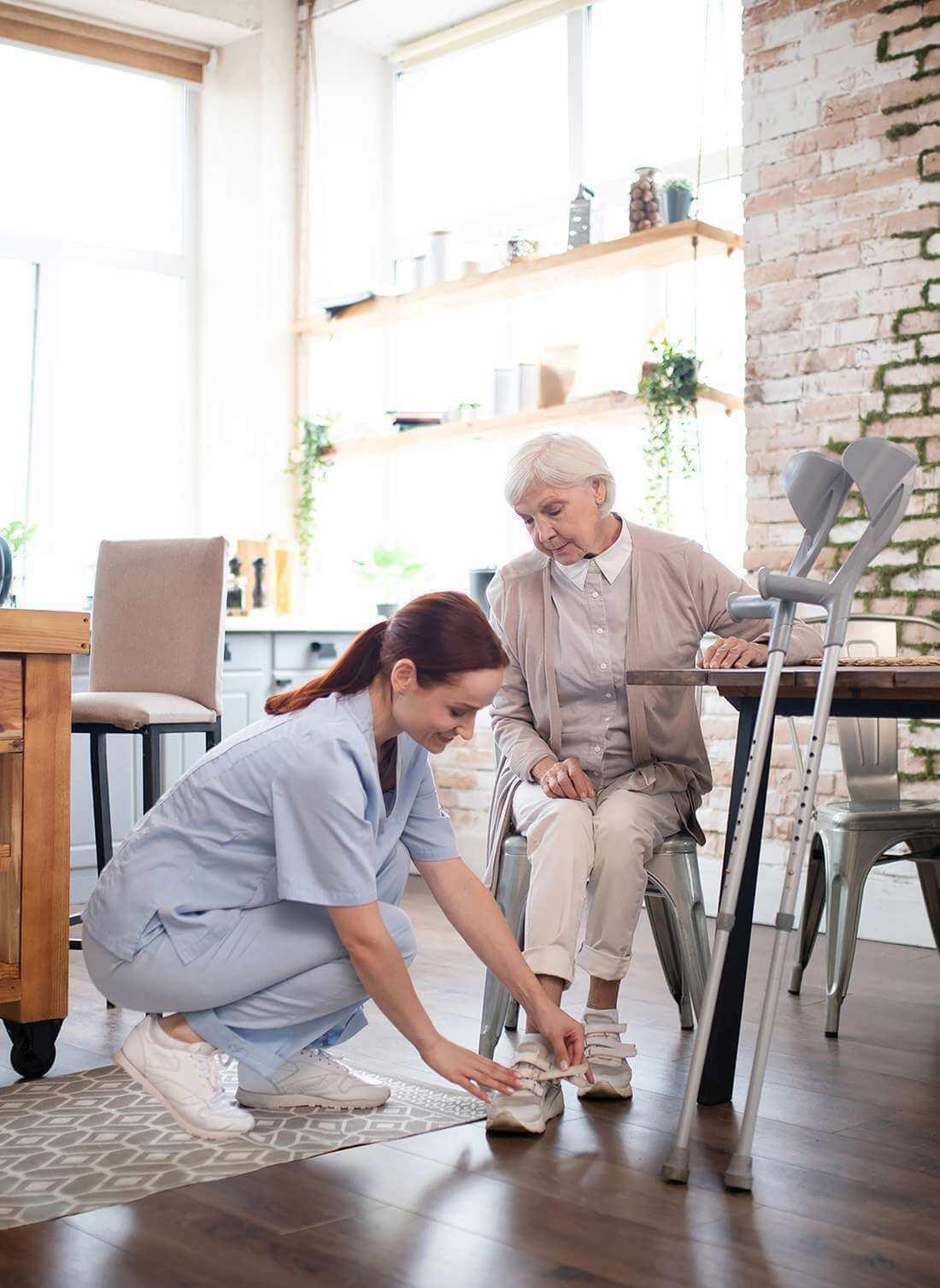 Fleissige Pflegerin zieht einer älteren Dame die Schuhe für einen Spaziergang in Basel an.
