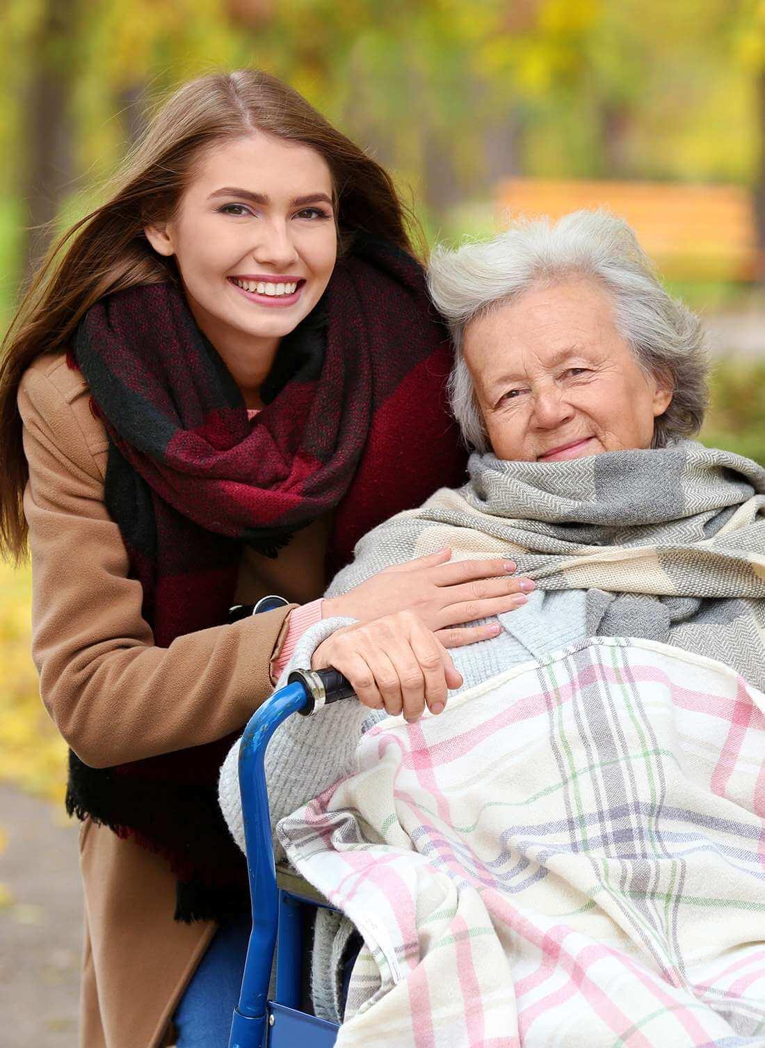 Glückliche Seniorin mit ihrer Enkelin im Park, dank professioneller Beratung und Unterstützung.