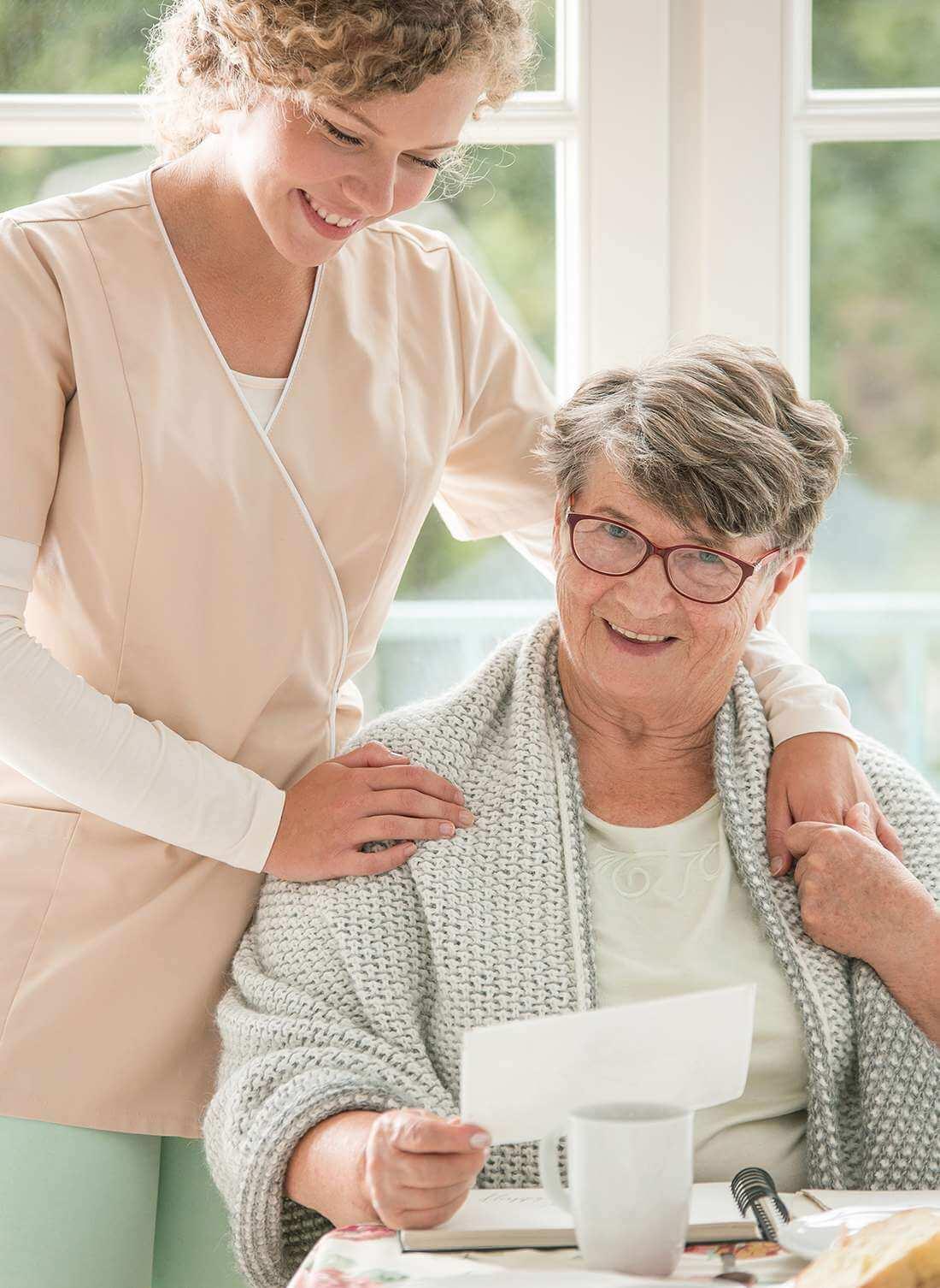 Seniorin wird von ihrer Pflegekraft bei der Erledigung der täglich anfallenden Aufgaben liebevoll unterstützt.